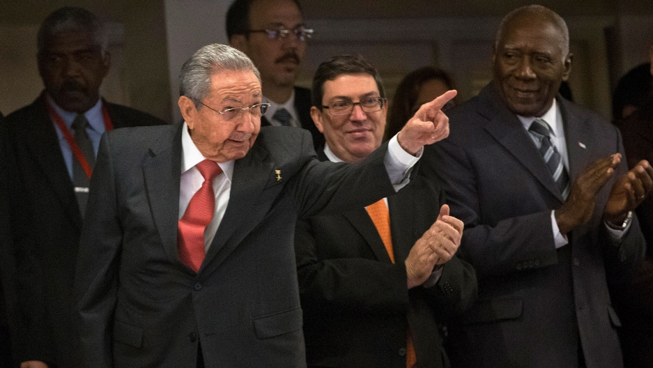 Raúl Castro is shown wearing a dark suit and red tie with his left arm raised and finger pointing.
