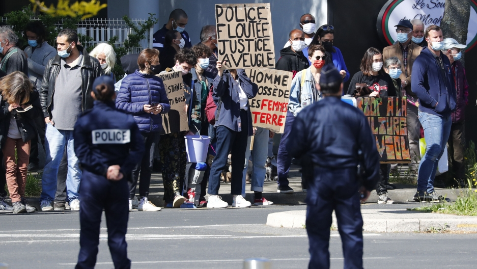 Two uniformed police stand before a crowd of protesters holding banners and signs