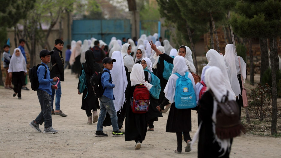 A crowd of young people are shown walking near a school with many girls wearing a white head covering.