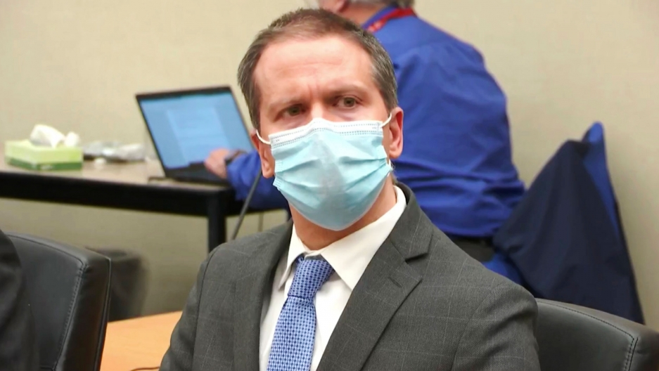 In this image from video, defendant, former Minneapolis police Officer Derek Chauvin is shown wearing a face mask, gray suit and blue tie.
