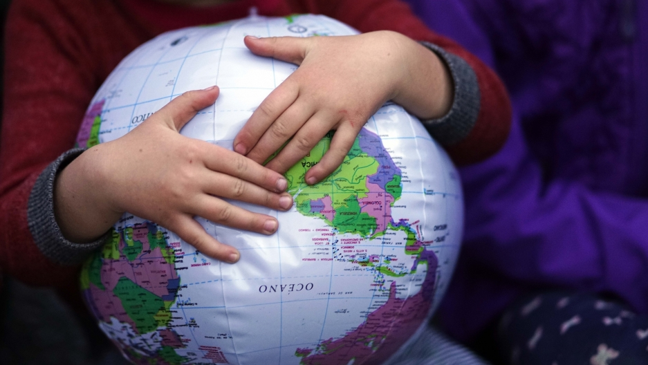 Child holds onto an inflatable globe