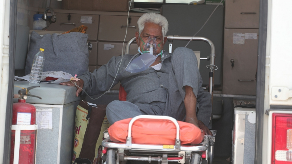 An older man is shown sitting on a gurney with a face mask on supplying oxygen.