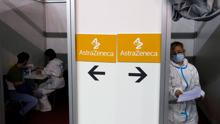 Medical professionals are shown on either side of a wall that has signs for the AstraZeneca vaccine posted on it.