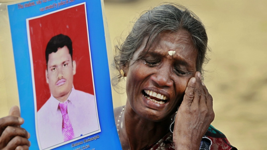 A woman weeps while holding a picture of her dead son, with a hand to her cheek, and eyes closed.