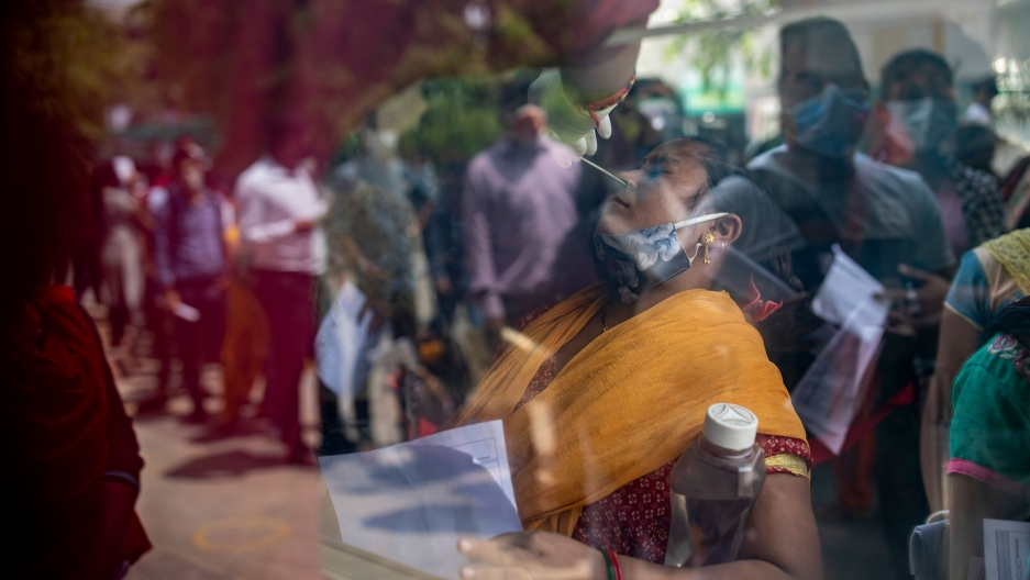 A woman wearing a yellow sari is shown through a window with her head leaned back and long swab in her nose.