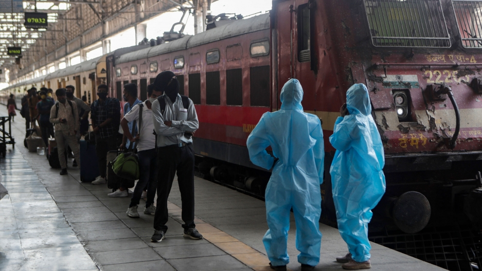 A long line of people are shown standing next to a train with two health care workers, shown at the end of the platform, wearing protective clothing.