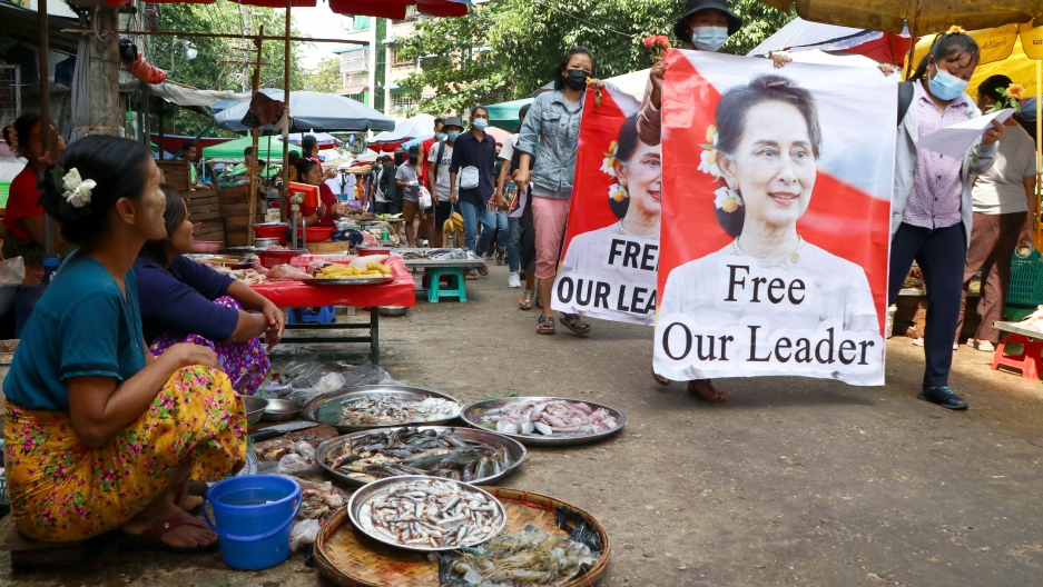 Anti-coup protesters walk through a market with images of ousted Myanmar leader Aung San Suu Kyi at Kamayut township in Yangon, Myanmar, April 8, 2021. They walked through the markets and streets of Kamayut township with slogans to show their disaffection