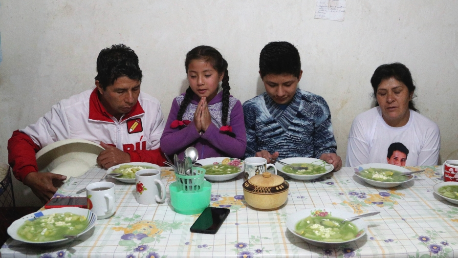 Free Peru party presidential candidate Pedro Castillo, from left, daughter Alondra, son Arnold and wife Lilia Paredes, pray before eating breakfast, in their home in Chugur, Peru, April 16, 2021. Castillo, a rural teacher, who has proposed rewriting Peru'