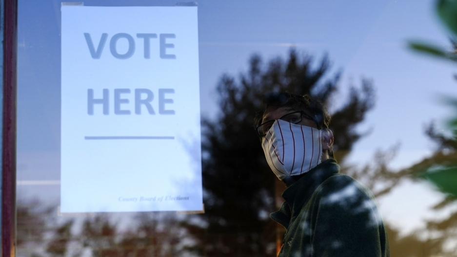 Vote sign in a window with masked man looking at it in reflection