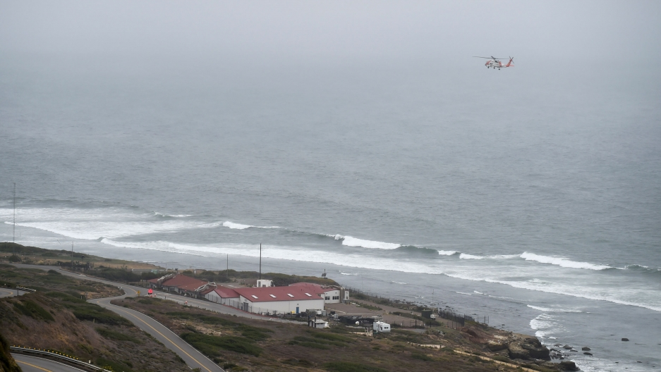 Waves are shown crashing into San Diego's coastline with a rescue helicopter flying above.