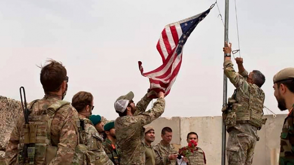 A small group of soliders are shown wearing military fatigues while one man is taking a US flag down off a flagpole