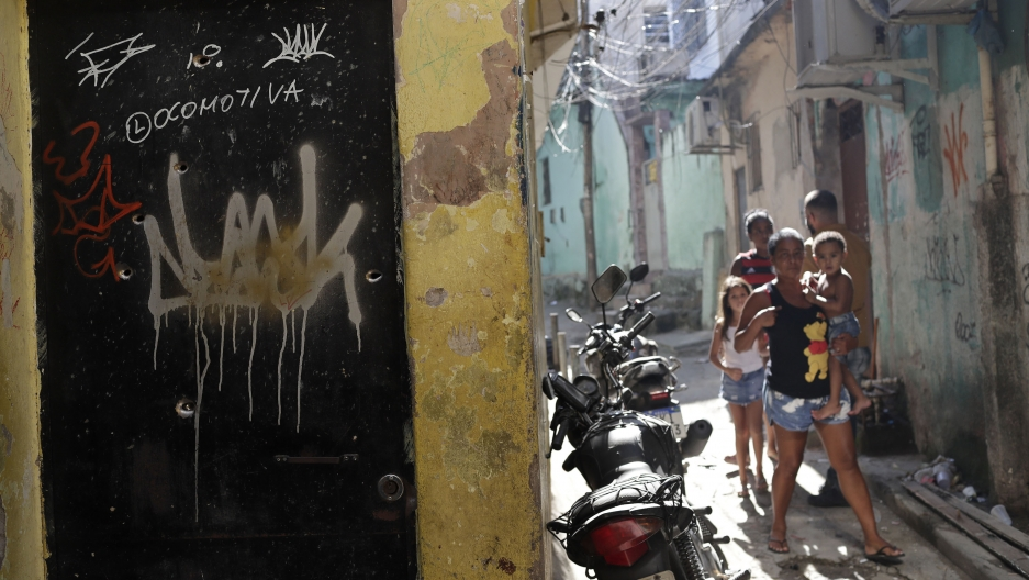 Residents walk near a doorway scared with bullet holes after a police raid against alleged drug traffickers in Rio de Janeiro, Brazil, May 6, 2021.