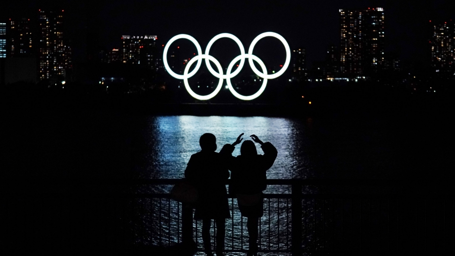 Two people are shown standing at a railing next to a body of water where the Olympic rings are in the destance illuminated in white.