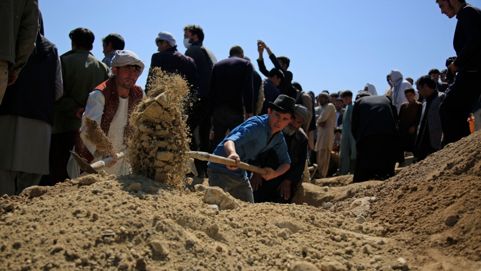 A large crowd of people are show at a cemetery as a man holds a shovel and is digging a burial site.