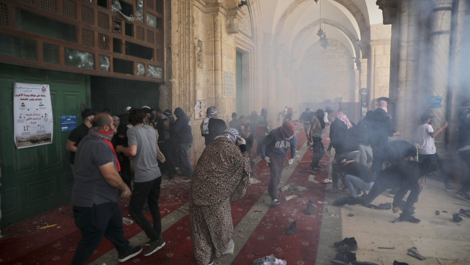 A large crowd of people are shown scattered in the Al-Aqsa Mosque as tear gas is shown surround the area.