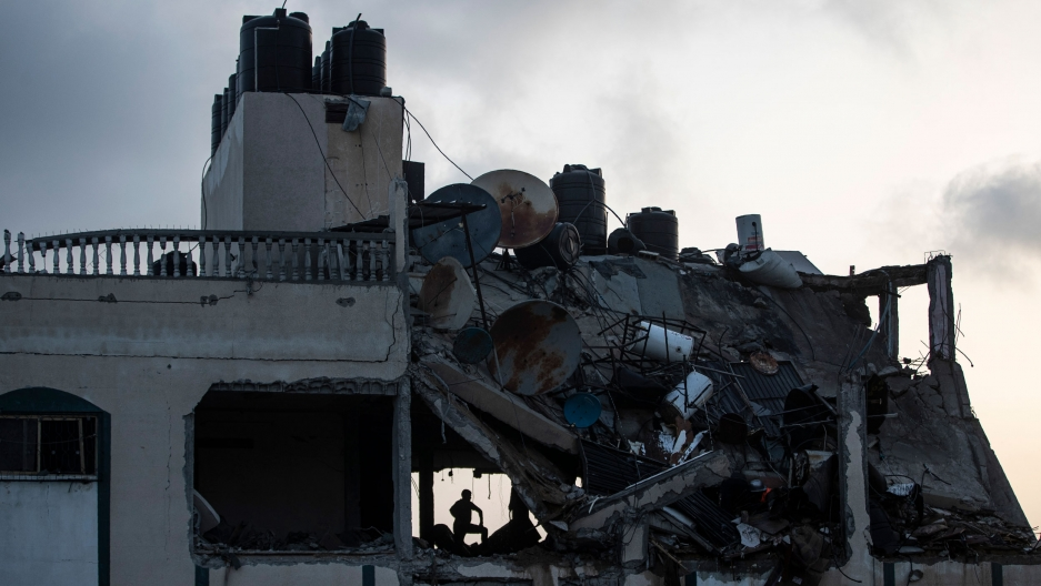A person is shown in shadow in a blown out window in the collapsed section of a building.