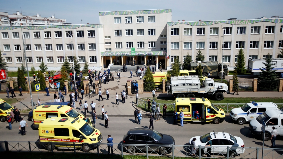 Several yellow ambulances and white police cars and are shown in the street outside of a three storey school building.
