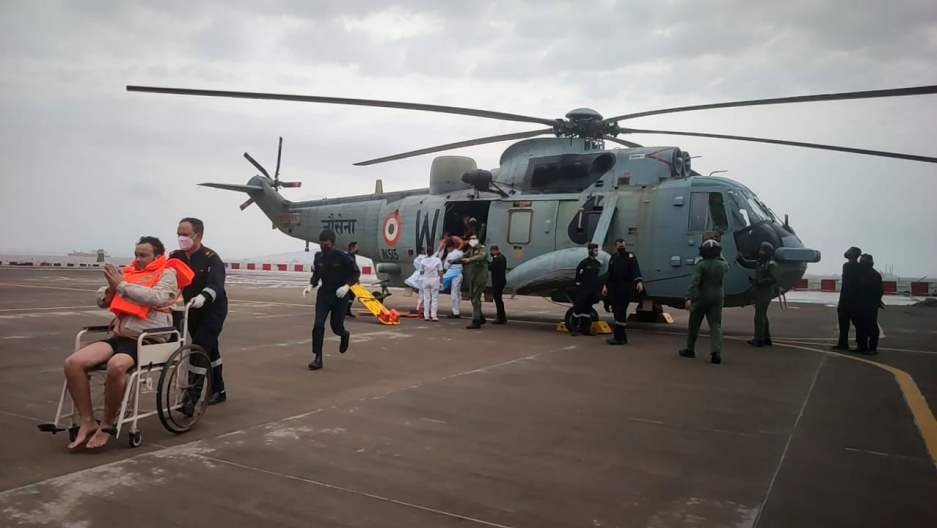 A large military rescue helicopter is shown in the distance with a man wearing a PFD is wheeled on a tarmac.