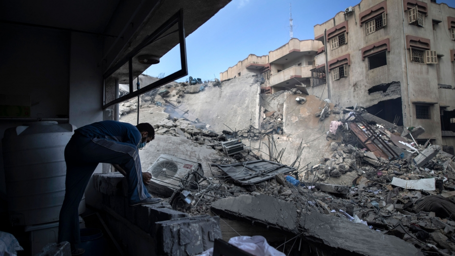 A man is shown bending over and looking at the remains of a bombed out building with rubble scatter all over.