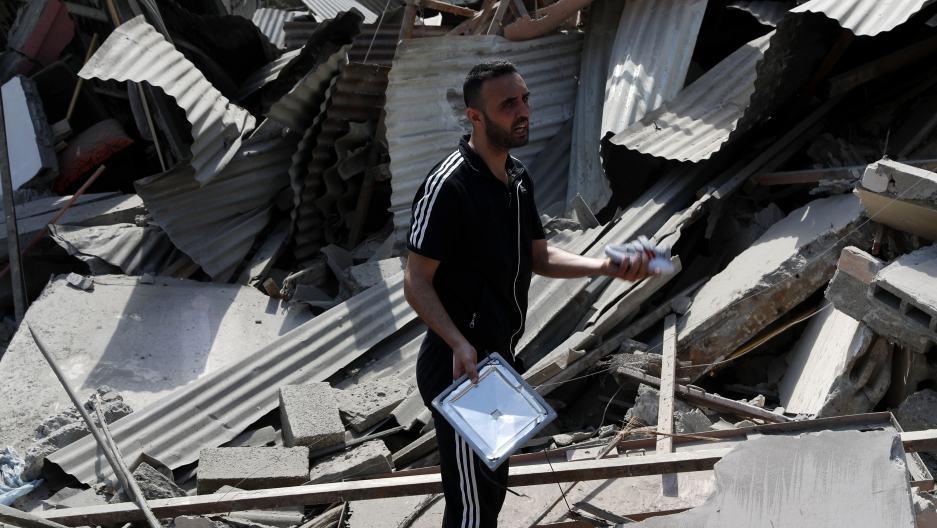 A man inspects the rubble of destroyed residential building, which was hit by Israeli airstrikes, in Gaza City