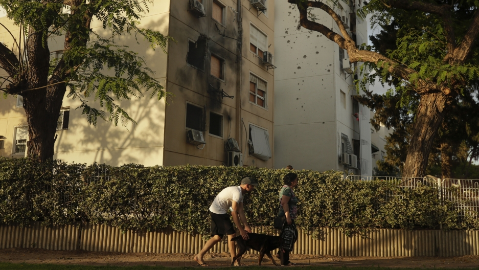 People walk by a damaged residential building after it was hit by a rocket fired from the Gaza Strip.