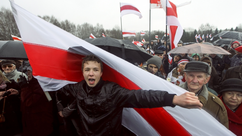 Man in black jacket holding red and white flag