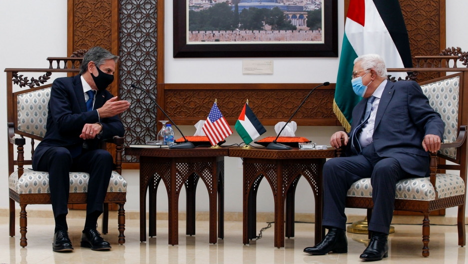 Palestinian President Mahmoud Abbas and US Secretary of State Antony Blinken are show sitting in opposite armchairs with two wooden side tables between them.