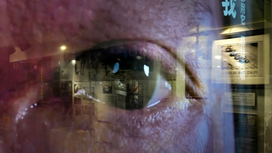 A close of photograph showing a person's eye and seen through clear glass reflecting the image of a gallery exhibit.
