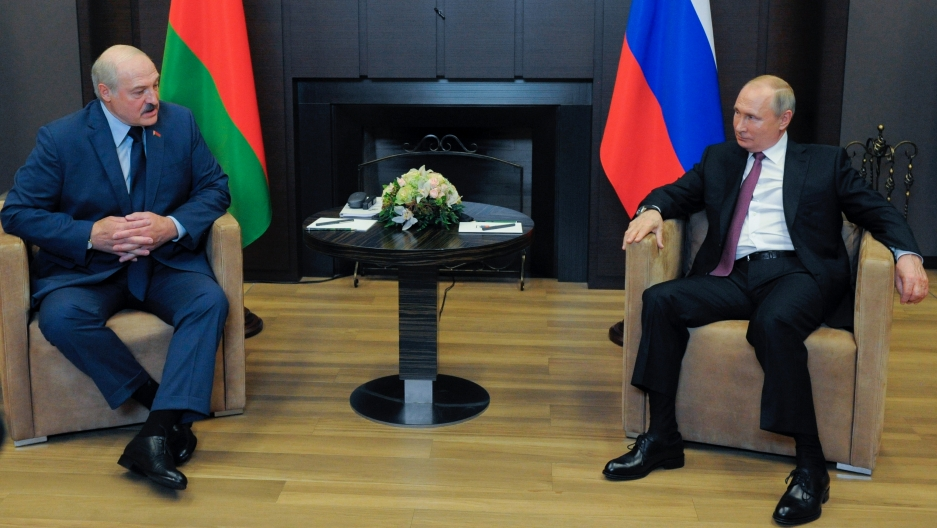 Russian President Vladimir Putin, right, and Belarusian President Alexander Lukashenko talk to each other during their meeting in the Black Sea resort of Sochi, Russia