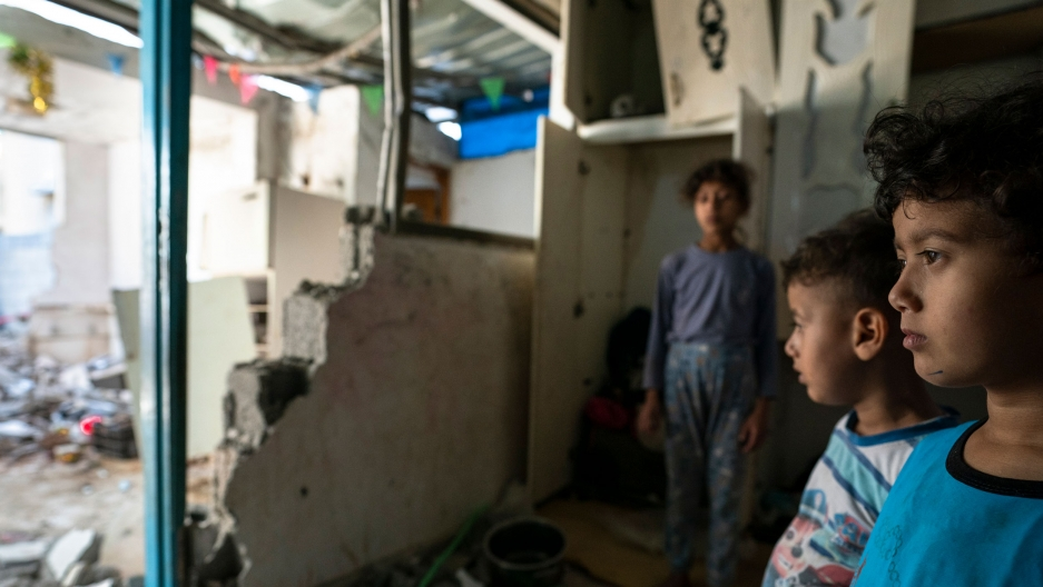 Three young children are shown looking off to a room damaged by rocket attack.