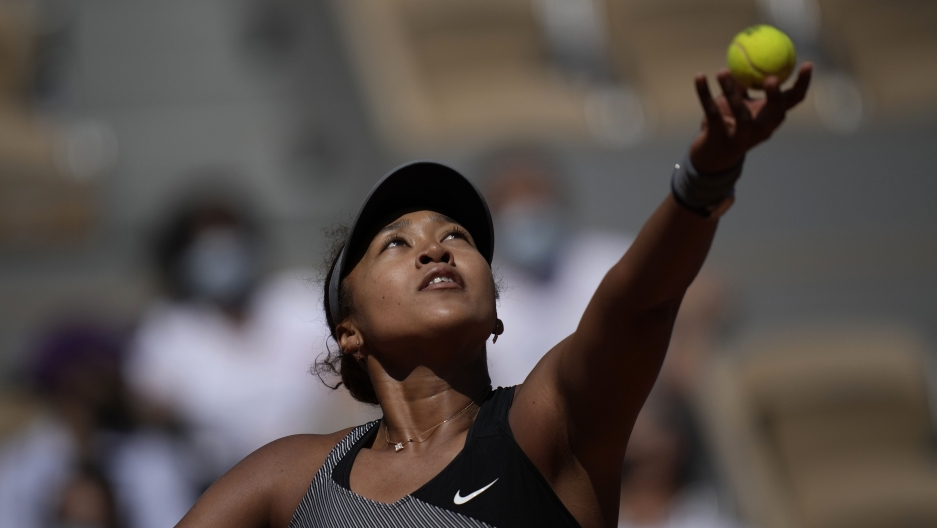 A tennis player lifts her ball and racket into the air.