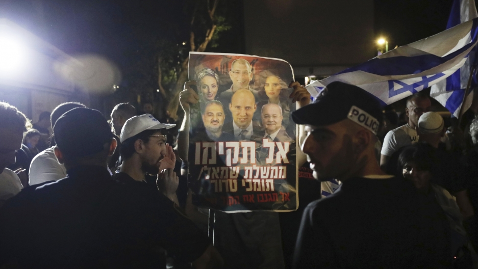 Israeli police officers stand guard as right-wing protesters chant slogans and hold signs.