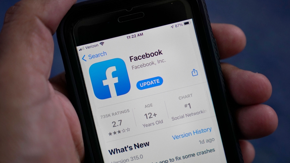 """Facebook's square blue logo with a white """"F"""" is shown at the top of the app's update page on a mobile phone."""