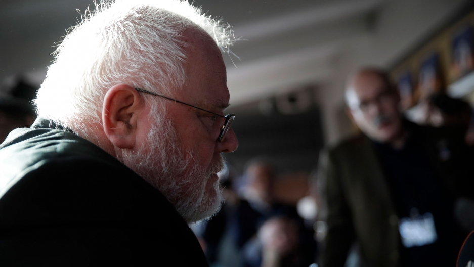 Cardinal Reinhard Marx, who has white hair and beard, is shown in a profile view wearing glasses and sitting.