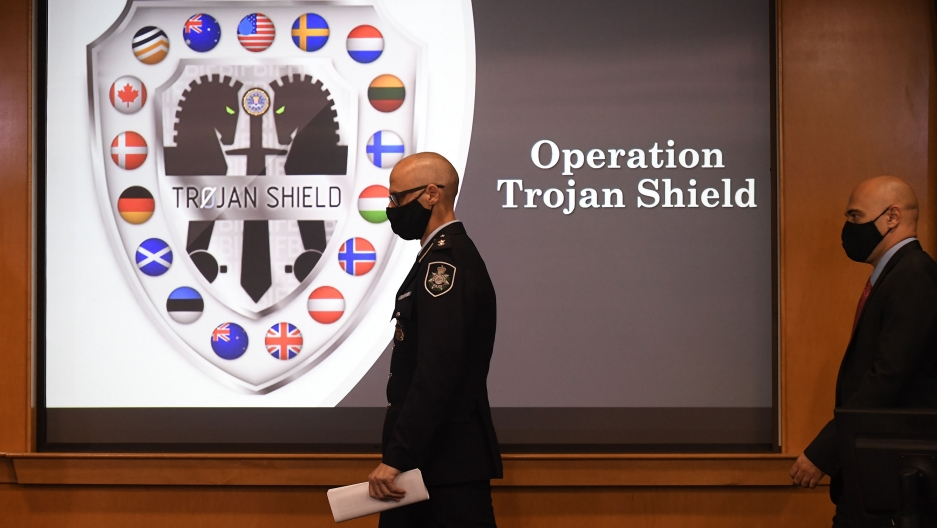 Law enforcement officials walk past an Operation Trojan Shield logo at a news conference, Tuesday, June 8, 2021, in San Diego.