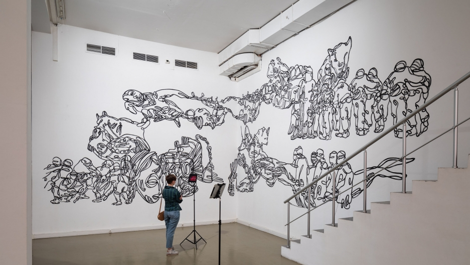 A white wall with black ink drawings and a person standing to view it