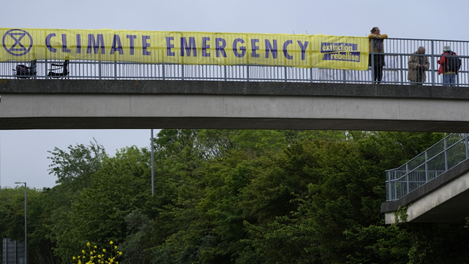 A climate banner covers the side of an overpass on a road leading to the G-7 summit near St. Ives, Cornwall, England, Thursday, June 10, 2021.