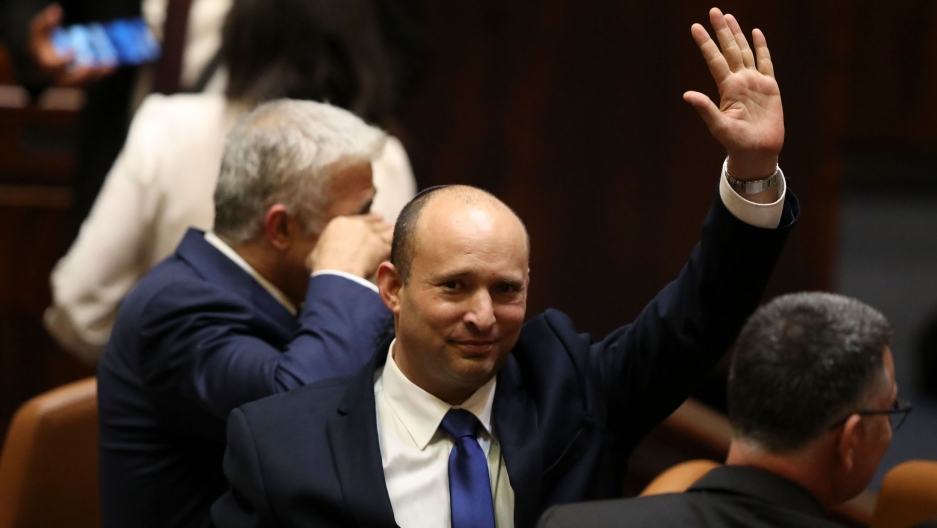 Naftali Bennett is shown wearing a dark suit and raising his right hand in the air.