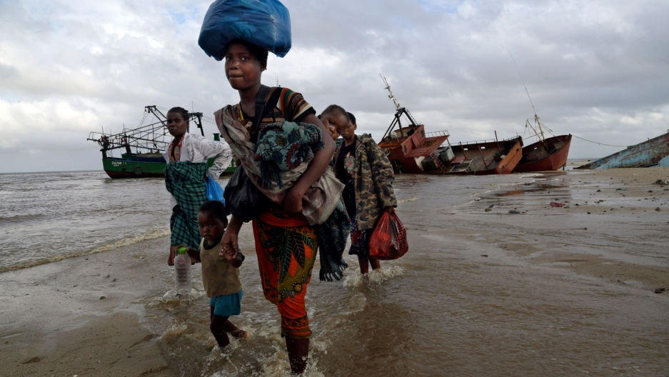 A small group of people are shown walking through coastal waters in Mozambique with large ships in the distance.