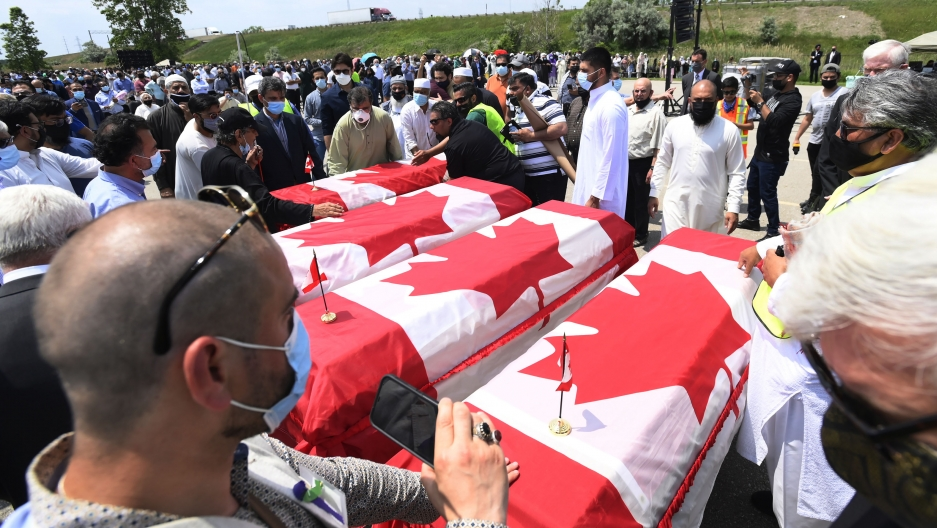Four caskets are covered with the Canadian flag of red and white as mourners look on.