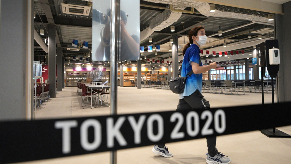 """A woman is shown walking and wearing a face mask and blue t-shirt in a nearly empty dining hall with a sign in the nearground that says """"Tokyo 2020."""""""