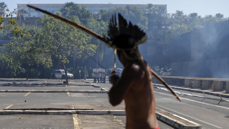 An Indigenous protester aims his bow an arrow at police outside Congress in Brasilia, Brazil, Tuesday, June 22, 2021.
