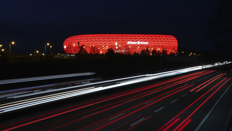 """In this Monday, March 16, 2020, file photo, cars pass the illuminated """"Allianz Arena""""soccer stadium in Munich, Germany."""