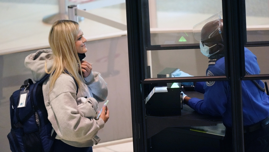 A traveler smiles as they pull down their mask for a TSA agent to confirm their identity at the security checkpoint at Love Field airport Friday, May 28, 2021, in Dallas.