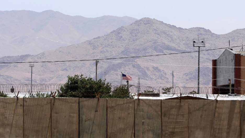 A large security wall is shown in the nearground with the US flag flying and a mountain range in the distance.
