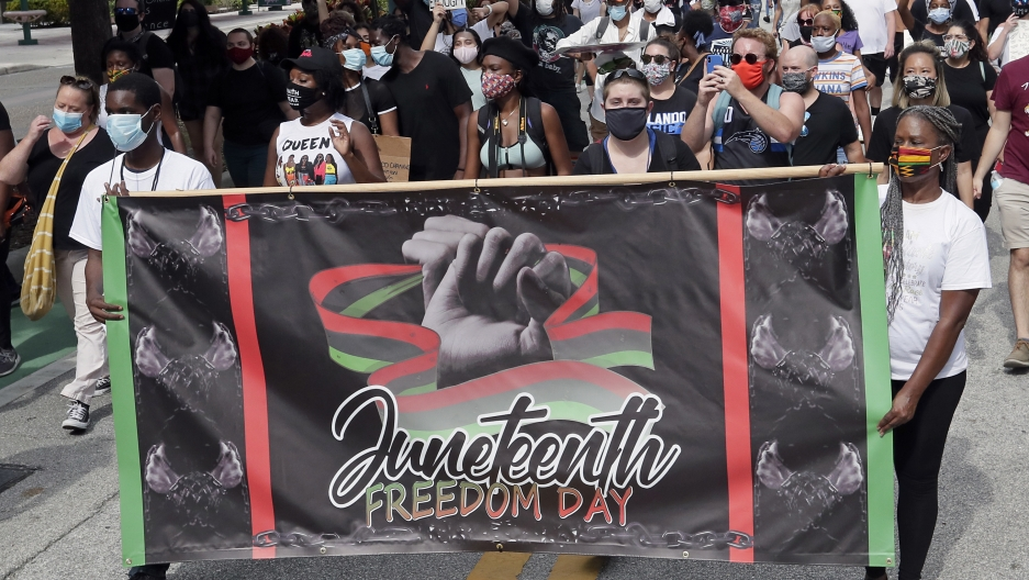 Demonstrators march through downtown Orlando, Florida, during a Juneteenth event,June 19, 2020.