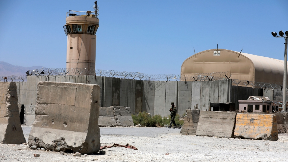 A tall control tower is shown with large concrete barriers on the ground nearby with barbed wire on top.