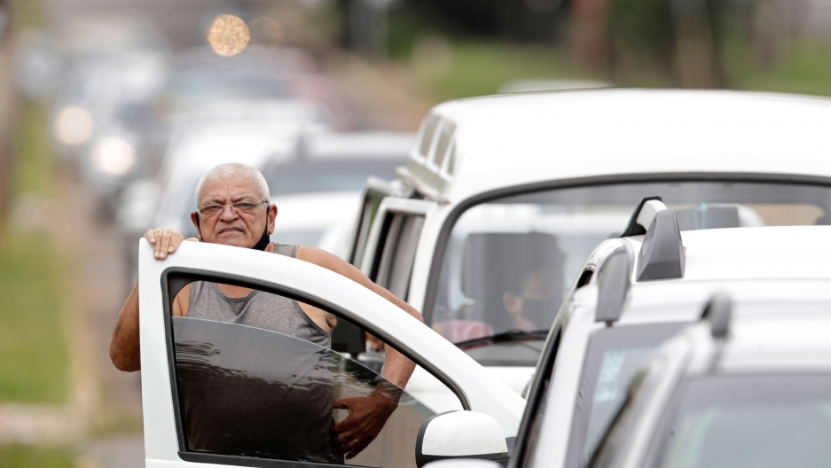In this March 22, 2021 file photo, a man stands next to his vehicle in a line at a COVID-19 vaccination point for priority elderly persons in the Ceilandia neighborhood, on the outskirts of Brasilia, Brazil.