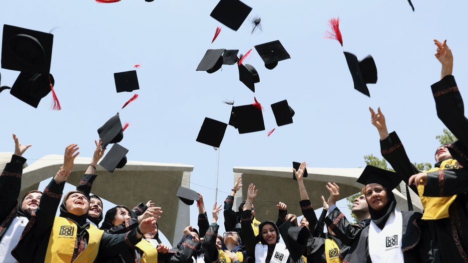 Students throw their hats in the air to celebrate a graduation in front of the main gate of Tehran University in Tehran, Iran, July 7, 2019.