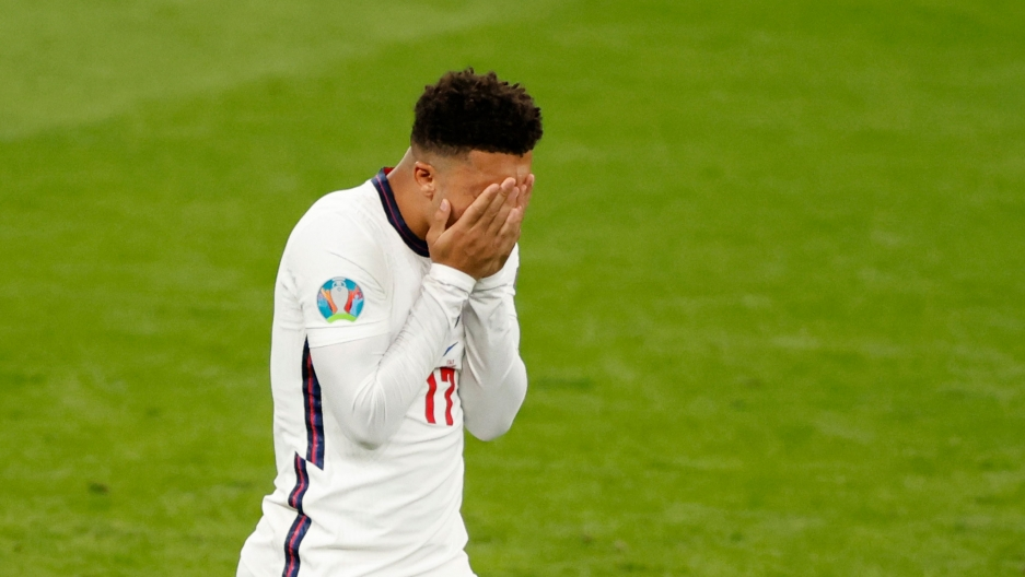 England's Jadon Sancho is shown on the soccer pitch holding his hands to his face.